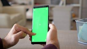 Άτομο που κρατά ένα smartphone στα χέρια με την πράσινη χλεύη χρώματος οθόνης επάνω απόθεμα βίντεο