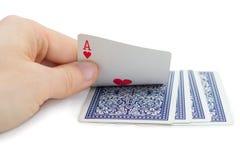 Άτομο που κρατά και που κρυφοκοιτάζει μια κάρτα παιχνιδιού (άσσος των καρδιών) Στοκ Φωτογραφία