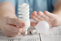 Άτομο που κρατά μια ενέργεια - λαμπτήρας αποταμίευσης και κανονική λάμπα φωτός απορριμάτων Στοκ φωτογραφίες με δικαίωμα ελεύθερης χρήσης