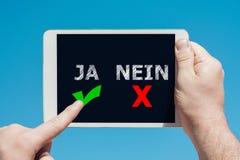 Άτομο που κρατά μια συσκευή ταμπλετών με τα εικονίδια ` ναι αριθ. ` στα γερμανικά ως έννοια απόφασης Στοκ Φωτογραφίες
