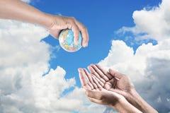 Άτομο που κρατά μια σφαίρα στα χέρια του δώστε τη γη στον άνθρωπο στον ουρανό Στοκ εικόνες με δικαίωμα ελεύθερης χρήσης