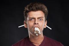 Άτομο που κρατά πολλά τσιγάρα στο στόμα του Στοκ Φωτογραφία