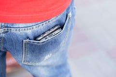 Άτομο που κρατά τα κινητά τηλέφωνα unsafety στον τρόπο στην πίσω τσέπη, ea Στοκ φωτογραφία με δικαίωμα ελεύθερης χρήσης