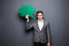Άτομο που κρατά την πράσινη κενή λεκτική φυσαλίδα με το διάστημα για το κείμενο στο γκρίζο υπόβαθρο Στοκ Εικόνα