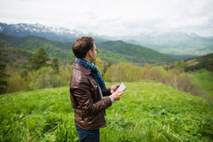 Άτομο που κρατά την ψηφιακή ταμπλέτα στην κορυφή βουνών Στοκ εικόνα με δικαίωμα ελεύθερης χρήσης