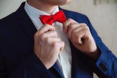 Άτομο που κρατά τον κόκκινους δεσμό τόξων και τον επίδεσμο Κομψός κύριος clother Στοκ φωτογραφία με δικαίωμα ελεύθερης χρήσης
