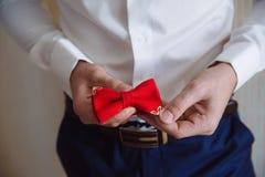 Άτομο που κρατά τον κόκκινο δεσμό τόξων Κομψός κύριος clother Στοκ Φωτογραφία