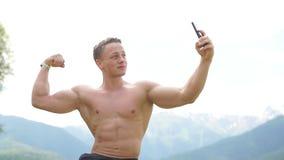 Άτομο που κρατά το έξυπνο τηλέφωνο και που παίρνει ένα selfie υπαίθρια πέρα από τη φύση βουνών απόθεμα βίντεο