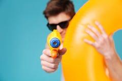 Άτομο που κρατά το διογκώσιμο δαχτυλίδι και που δείχνει το πυροβόλο όπλο νερού στη κάμερα Στοκ φωτογραφία με δικαίωμα ελεύθερης χρήσης