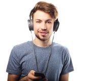 Άτομο που κρατά το κινητό τηλέφωνο και που στη μουσική πέρα από το άσπρο backg στοκ φωτογραφίες με δικαίωμα ελεύθερης χρήσης