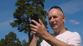 Άτομο που κρατά το κινητό τηλέφωνο και που χρησιμοποιεί τη τηλεσύσκεψη για την επικοινωνία υπαίθρια φιλμ μικρού μήκους