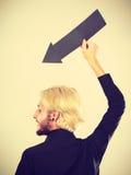 Άτομο που κρατά το μαύρο βέλος δείχνοντας αριστερά κάτω Στοκ Φωτογραφίες