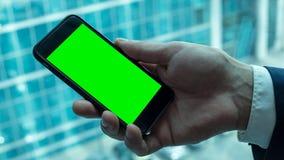 Άτομο που κρατά το μαύρο smartphone με την πράσινη οθόνη κοντά στο παράθυρο Στοκ Φωτογραφίες