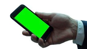 Άτομο που κρατά το μαύρο smartphone με την πράσινη οθόνη Στοκ φωτογραφία με δικαίωμα ελεύθερης χρήσης