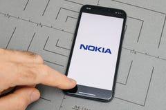 Άτομο που κρατά το νέο iphone Apple Χ 10 με τη Nokia, τηλεπικοινωνίες app λογότυπων Στοκ φωτογραφίες με δικαίωμα ελεύθερης χρήσης