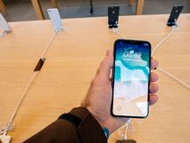 Άτομο που κρατά το πιό πρόσφατο iPhone Χ στη Apple Store στην έναρξη Στοκ Φωτογραφία