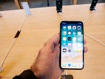 Άτομο που κρατά το πιό πρόσφατο iPhone Χ στη Apple Store στην έναρξη Στοκ Εικόνες
