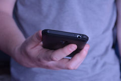 Άτομο που κρατά το τηλέφωνο και που δακτυλογραφεί το μήνυμα Στοκ φωτογραφίες με δικαίωμα ελεύθερης χρήσης