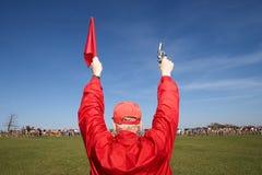 Άτομο που κρατά ψηλά ένα πυροβόλο όπλο και μια σημαία εκκινητών στοκ φωτογραφία με δικαίωμα ελεύθερης χρήσης