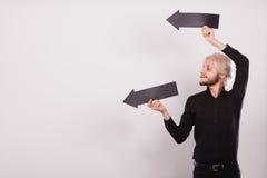 Άτομο που κρατά δύο βέλη που δείχνουν την ίδια κατεύθυνση Στοκ Φωτογραφίες