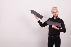 Άτομο που κρατά δύο βέλη που δείχνουν την ίδια κατεύθυνση Στοκ Εικόνες