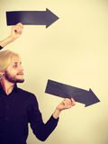 Άτομο που κρατά δύο βέλη που δείχνουν την ίδια κατεύθυνση Στοκ εικόνες με δικαίωμα ελεύθερης χρήσης