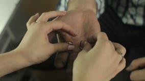 Άτομο που κρατά δύο γαμήλια δαχτυλίδια στα χέρια του, που παρουσιάζουν γαμήλιο δαχτυλίδι στη νύφη του φιλμ μικρού μήκους