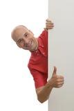 Άτομο που κρυφοκοιτάζει πίσω από την κενή αφίσα Στοκ Εικόνα