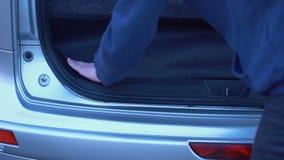 Άτομο που κρύβει τα απαγορευμένα πακέτα στον κορμό αυτοκινήτων, λαθραίο πέρασμα ναρκωτικών, παράνομες εμπορικές συναλλαγές απόθεμα βίντεο