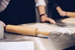 Άτομο που κυλά την ακατέργαστη ζύμη με την κυλώντας καρφίτσα Στοκ εικόνες με δικαίωμα ελεύθερης χρήσης