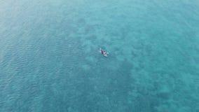 Άτομο που κωπηλατεί στη βάρκα πέρα από την τυρκουάζ θάλασσα εναέρια όψη απόθεμα βίντεο