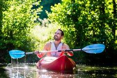 Άτομο που κωπηλατεί με το καγιάκ στον ποταμό για τον αθλητισμό νερού στοκ εικόνες