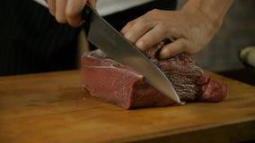 Άτομο που κόβει ένα κομμάτι του φρέσκου κρέατος απόθεμα βίντεο
