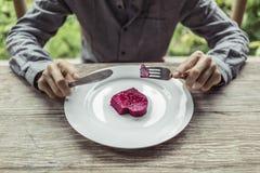 Άτομο που κόβει την καρδιά στο πιάτο Στοκ Φωτογραφίες