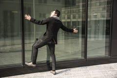 Άτομο που κλίνει ενάντια στο παράθυρο του κτιρίου γραφείων Στοκ εικόνα με δικαίωμα ελεύθερης χρήσης