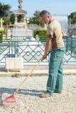 Άτομο που μαζεύει με τη τσουγκράνα το αμμοχάλικο στο νεκροταφείο στοκ εικόνες