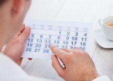 Άτομο που μαρκάρει με τη μάνδρα και που εξετάζει την ημερομηνία στο ημερολόγιο Στοκ Εικόνα