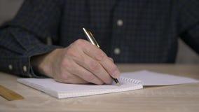 Άτομο που μελετά και που γράφει στο copybook με τη μάνδρα Κλείστε επάνω το χέρι ατόμων με τη μάνδρα γράφει κάτω τις σκέψεις στο σ απόθεμα βίντεο