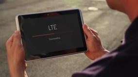 Άτομο που μεταφορτώνει το βίντεο άνω των LTE σε ένα PC ταμπλετών απόθεμα βίντεο