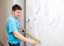 Άτομο που μετρά τον τοίχο με ένα μέτρο ταινιών Στοκ Φωτογραφία