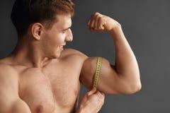Άτομο που μετρά τους δικέφαλους μυς σε γκρίζο Στοκ φωτογραφίες με δικαίωμα ελεύθερης χρήσης