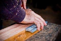 Άτομο που μετρά το ξύλο για την παραγωγή του χειροποίητου ατόμου εργαζόμενου σε έναν ξυλουργό με το στερεό ξύλο Στοκ εικόνα με δικαίωμα ελεύθερης χρήσης
