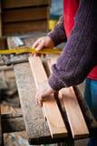 Άτομο που μετρά το ξύλο για την παραγωγή του χειροποίητου ατόμου εργαζόμενου σε έναν ξυλουργό με το στερεό ξύλο Στοκ Φωτογραφία
