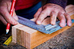 Άτομο που μετρά το ξύλο για την παραγωγή του χειροποίητου ατόμου εργαζόμενου σε έναν ξυλουργό με το στερεό ξύλο Στοκ Φωτογραφίες