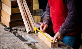 Άτομο που μετρά το ξύλο για την παραγωγή του χειροποίητου ατόμου εργαζόμενου σε έναν ξυλουργό με το στερεό ξύλο Στοκ Εικόνα