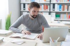 Άτομο που μελετά και που συνδέει με ένα lap-top στοκ εικόνες