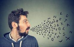 Άτομο που μιλά με τις επιστολές αλφάβητου που βγαίνουν από το στόμα του Στοκ Φωτογραφίες