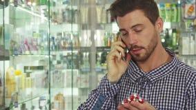Άτομο που μιλά στο τηλέφωνο για τα χάπια στο φαρμακείο φιλμ μικρού μήκους
