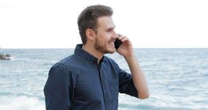Άτομο που μιλά στο τηλέφωνο που περπατά στην παραλία φιλμ μικρού μήκους