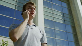Άτομο που μιλά από το κινητό τηλέφωνο στο υπόβαθρο της οικοδόμησης φιλμ μικρού μήκους